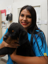 Our staff loves animals just like you do! Aby, receptionist, pictured with puppy Hercules